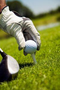 Hand_placing_golf_ball_on_tee.s600x600