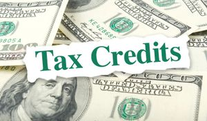 Tax credits text over 100 dollar bills