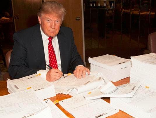 Donald Trump signing his huge tax return October 15 2015_Twitter2