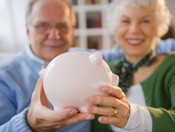 Older couple holding piggy bank
