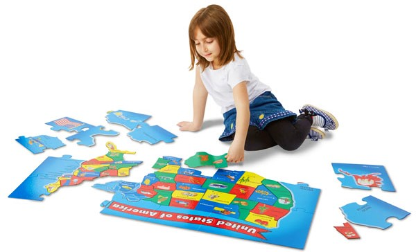 Girl putting together US map puzzle
