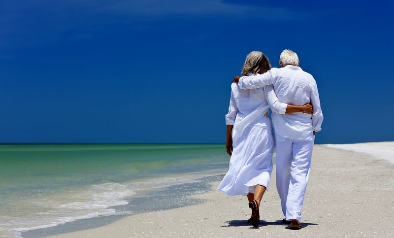 Retired couple beach walk