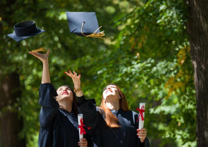 Graduates tossing mortarboards (2)