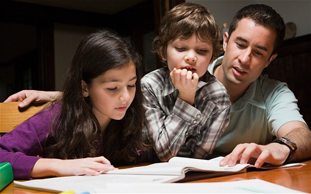 Dad helping daughter and son with homework