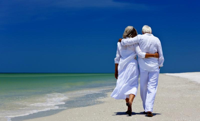 Retired couple walking along beach
