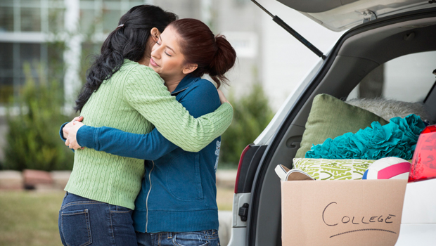 College-daughter hugging mome before heading to university