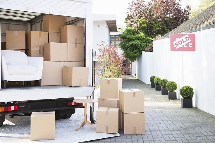 Moving boxes in van home sold sign