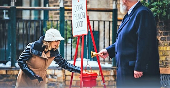 Donating to Salvation Army bell ringer red kettle