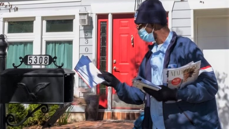 US Postal Service carrier with COVID19 face mask delivers mail