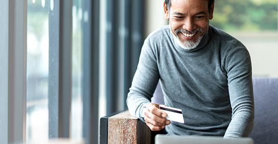Man using a credit card at a computer