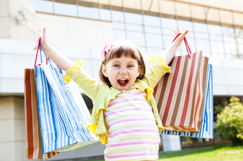 Happy young shopper_little girl shopping bags both hands