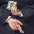 Tax cheating money crossed fingers behind back