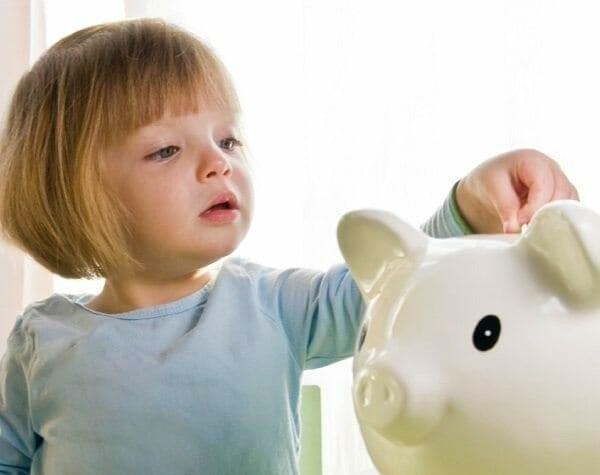 Young girl putting money in piggy bank