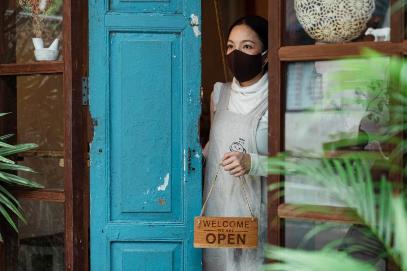 Woman in mask opening her store_pexels-ketut-subiyanto-4473090