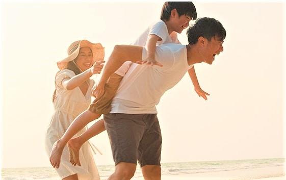 Mom dad and son having fun on beach