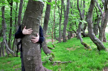 Man hiding sort of behind a tree