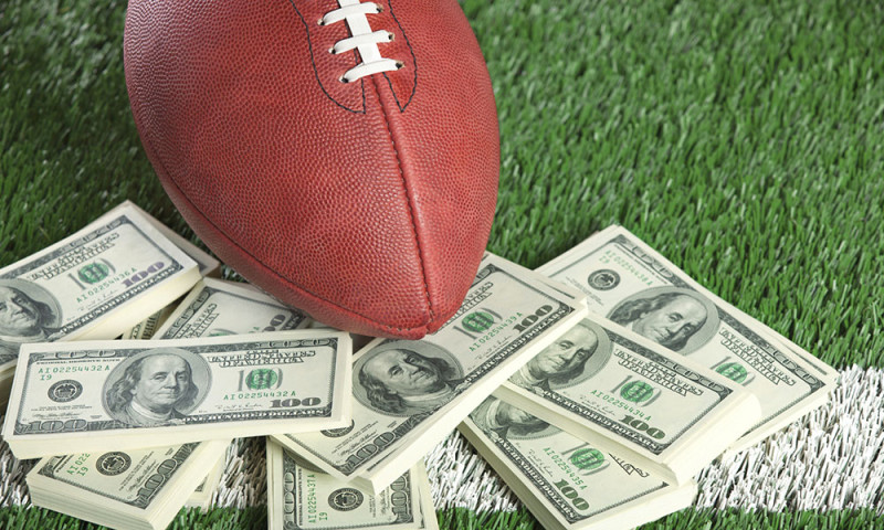 Football on field with stacks of cash_super-bowl-betting
