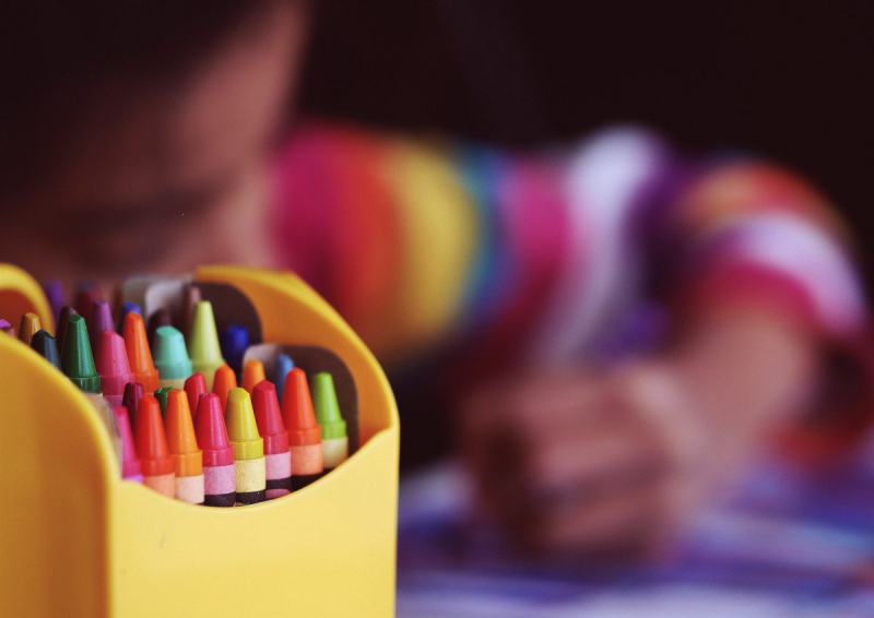 Crayons with kid coloring in the background