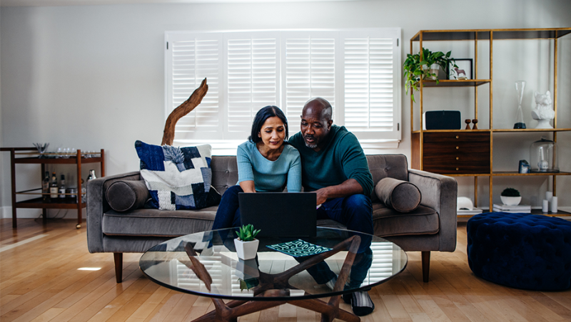 Middle aged couple at laptop in living room